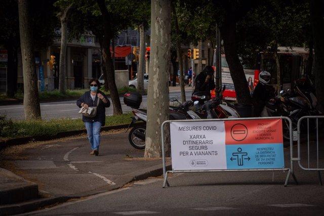 Una dona passa al costat de les tanques instal·lades per tallar el trànsit lateral de la Diagonal (Diagonal-Sant Joan). A Barcelona, Catalunya (Espanya), a 13 de maig de 2020.