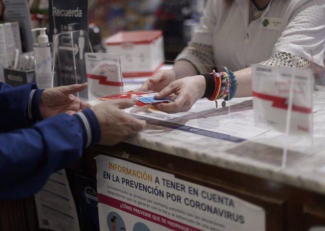 Una persona recoge una mascarilla de la Farmacia CEA, una de las 2.882 farmacias madrileñas que desde el pasado lunes han entregado de forma gratuita siete millones de mascarillas FFP2 modelo KN95. En Madrid, (España), a 12 de mayo de 2020.