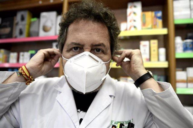 Un farmacéutico se coloca una de las siete millones de mascarillas FFP2 modelo KN95 que a partir de hoy las farmacias reparten gratuitamente entre la población de la Comunidad de Madrid. En Madrid (España), a 11 de mayo de 2020.