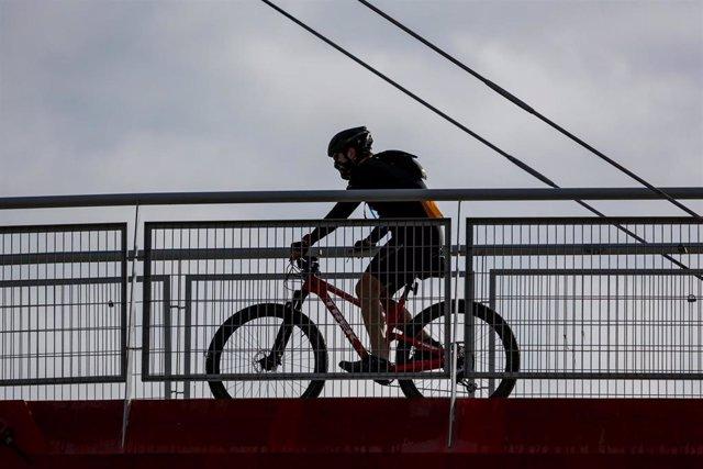 Un deportista sobre un puente en el primer día en que los españoles pueden salir de casa a pasear y hacer ejercicio al aire libre, pero solo en determinadas franjas horarias, divididos por edades, en el mismo municipio de residencia y sin alejarse en el c