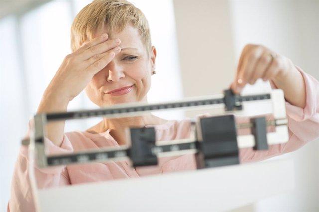 Mujer pesándose en una báscula.