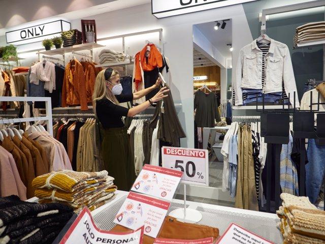 """Andrea Carrera, socia de las tiendas de moda """"Urban"""" de Pamplona, prepara el establecimiento para su reapeetura el próximo lunes, con la llegada de la fase 1 de la desescalada por el covid 19"""