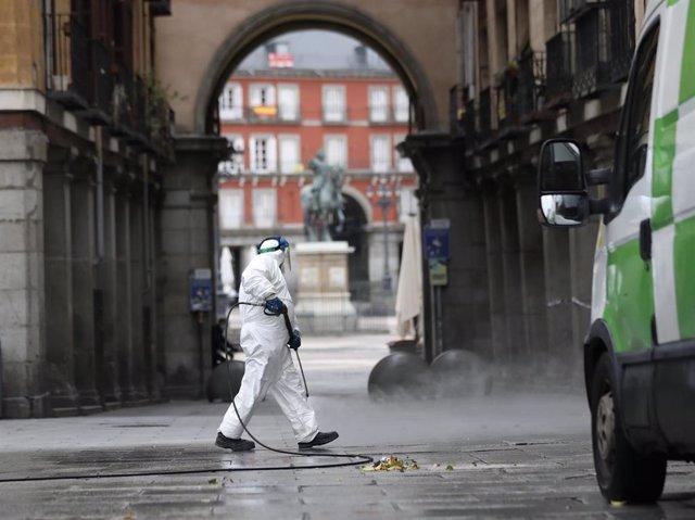 Un trabajador de la limpieza desinfecta las calles de la Plaza Mayor de la capital
