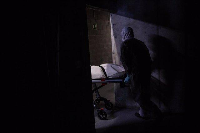Varios operarios protegidos de los Servicios Funerarios Memora trasladan un cuerpo de una residencia  en el garaje de una residencia de ancianos para recoger el cuerpo de una persona fallecida con Covid-19 para trasladarlo al Crematorio de Girona