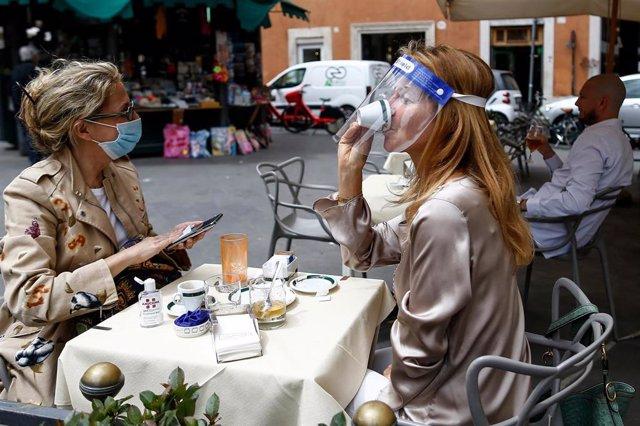 Dos personas sentadas en una terraza en Roma