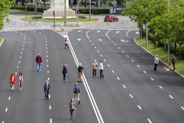 Transeúntes caminan por el paseo de Eduardo Dato de Madrid, una de las calles peatonalizadas en la capital a causa de la distancia de seguridad exigida por el COVID-19