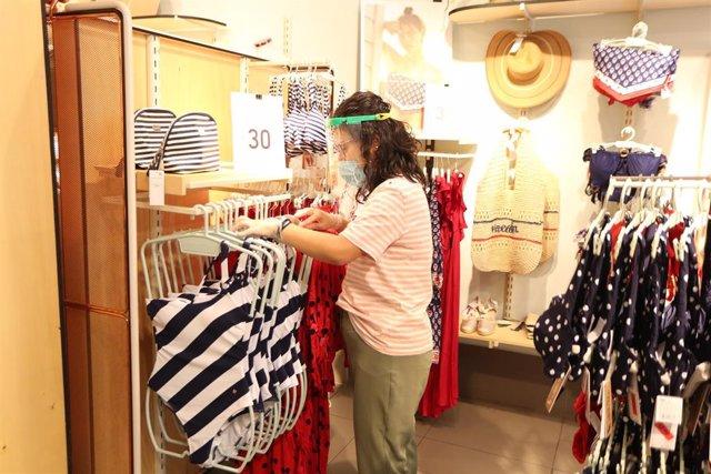Una trabajadora protegid con mascarilla trabaja colocando la zona de bañadores de una tienda de ropa