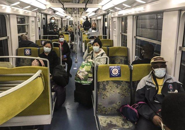 Gente con mascarilla en el metro de París
