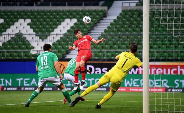 18 May 2020, Bremen: Leverkusen's Kai Havertz (C) scores against Bremen's goalkeeper Jiri Pavlenka (R) and Bremen's Milos Veljkovic during the German Bundesliga soccer match between Werder Bremen and Bayer Leverkusen at the Wohninvest Weser Stadium.