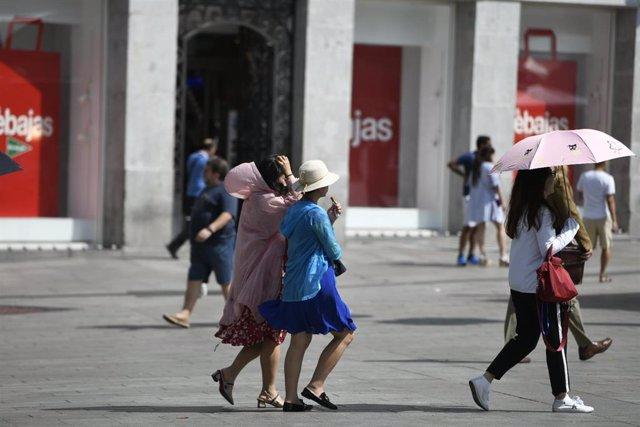 Turistas caminado en un día soleado en el centro de Madrid