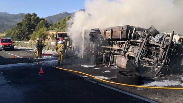 Los bomberos extinguen las llamas del camión.
