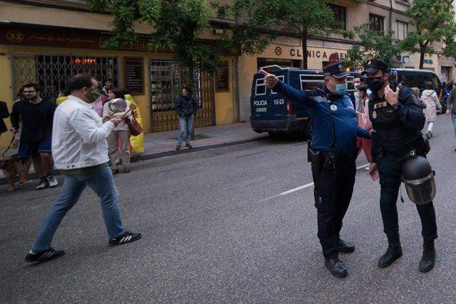 Un Policía Municipal hace indicaciones a un Policíamientras varias personas se manifiestan en la puerta de la sede del PSOE