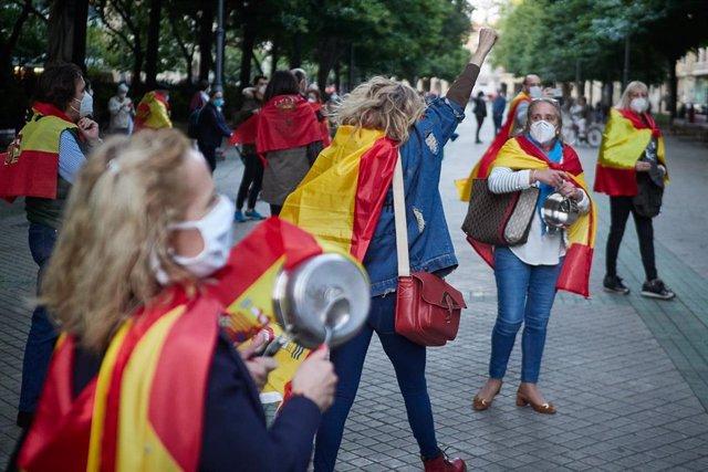 Varias personas asisten con banderas de España a la manifestación contra la gestión del Gobierno en la lucha contra el coronavirus Covid-19. En Pamplona, Navarra,  España, a 18 de mayo de 2020.