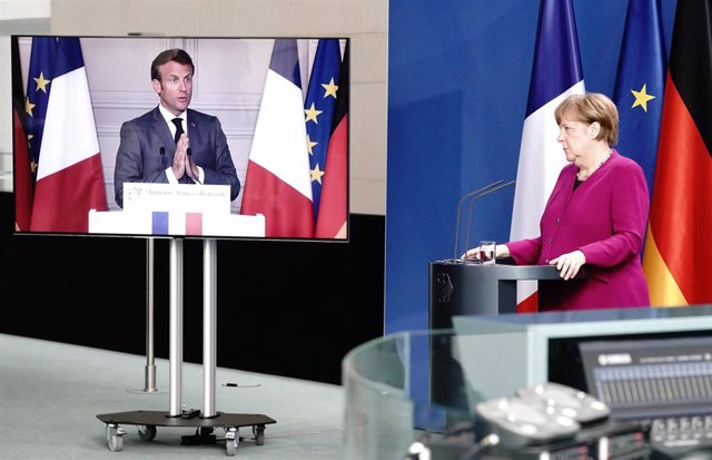 18 May 2020, Berlin: German Chancellor Angela Merkel listens as French President Emmanuel Macron (video-connected) speaks during a joint press conference. Photo: Kay Nietfeld/dpa-Pool/dpa