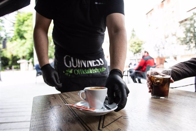 Un camarero sirve un café en una terraza en el centro de Vitoria (Álava)