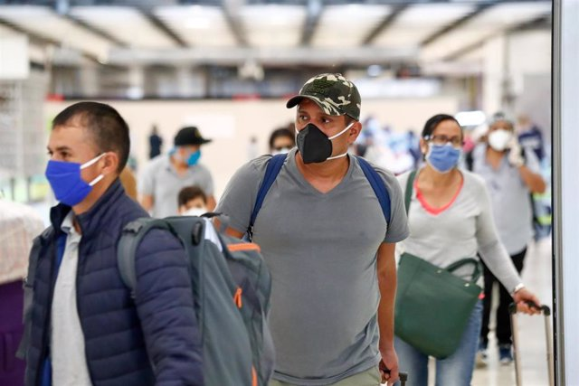 Varios pasajeros protegidos con mascarilla pasan los controles en la terminal 4 del Aeropuerto de Madrid-Barajas Adolfo Suárez