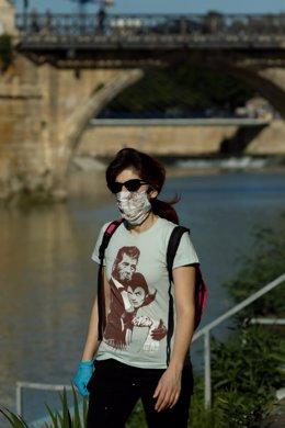 Un hombre pasea con mascarilla y guantes junto al río Segura