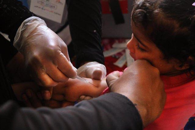 Una enfermera vacuna a una niña en Al-Atareb, Siria.