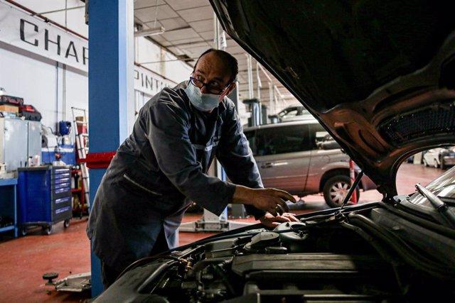 Un trabajador inspecciona un vehículo en talleres Otman