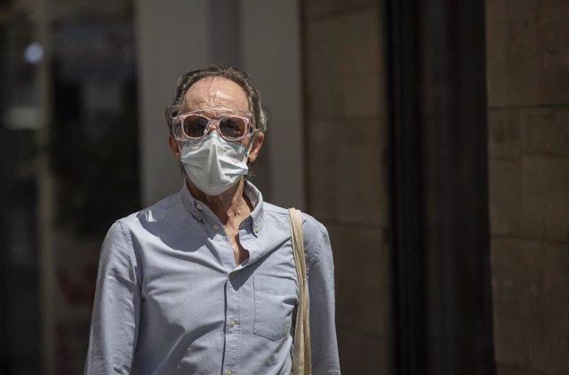 Un hombe protegido con mascarilla en una calle del centro de la ciudad. En Sevilla, (Andalucía, España), a 19 de mayo de 2020.