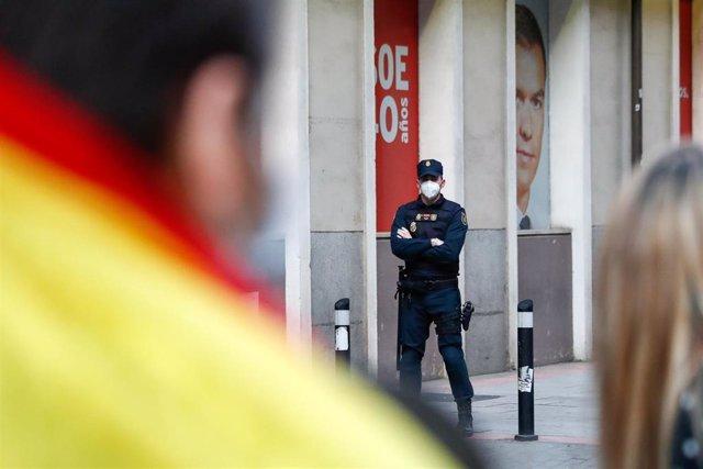 Un agente de la Policía en la sede del PSOE en una de las protestas contra el estado de alarma por el coronavirus