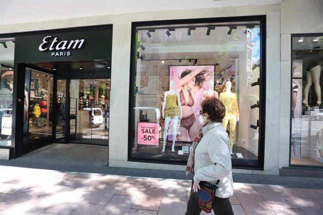 Una mujer pasa junto a una tienda Etam en la que se anuncian rebajas de hasta  el 50% el día en el que el Gobierno permite finalmente las rebajas desde hoy en toda España siempre que no generen aglomeraciones, en Madrid (España) a 18 de mayo de 2020.