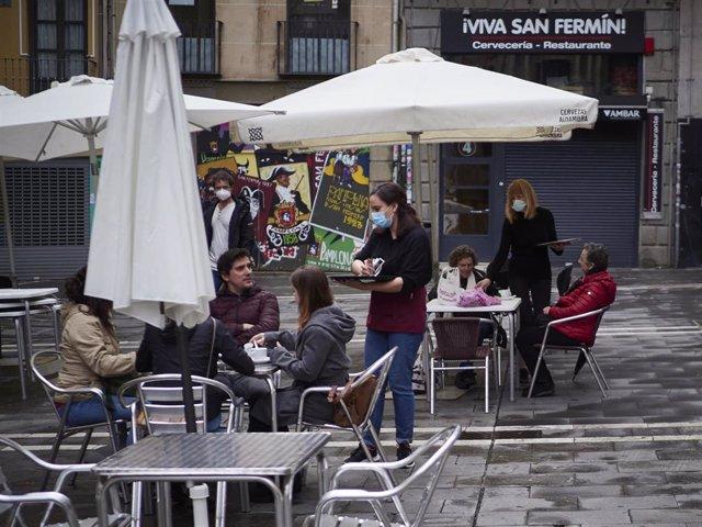 Una camarera atiende a varias personas sentadas en una terraza de Navarra donde los empleados utilizan un metro para asegurarse de que las medidas de distanciamiento son las correctas entre los potenciales clientes de la terraza de un bar en el centro de