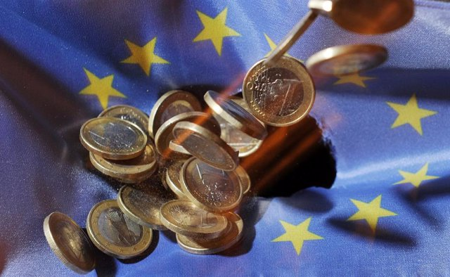 FILED - 04 July 2011, Baden-Wuerttemberg, Karlsruhe: One euro coins will fall onto an EU flag. The European Union's gross domestic product shrank 3.5 per cent in the first three months of the year, according to a first estimate from Eurostat, while eurozo