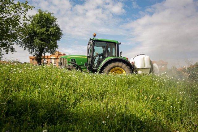 Un agricultor montado en su tractor desinfecta las inmediaciones de Aranjuez
