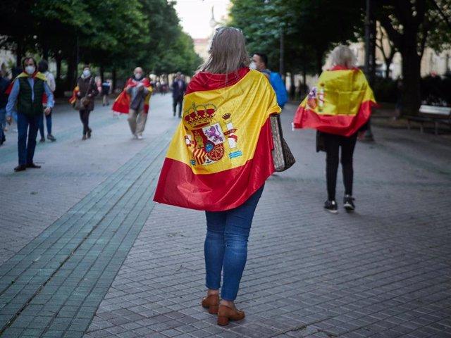 Varias personas asisten con banderas de España a una concentración contra la gestión del Gobierno en la lucha contra el coronavirus Covid-19.