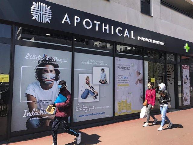 Una farmacia de Francia con un anuncio de mascarillas en su fachada.