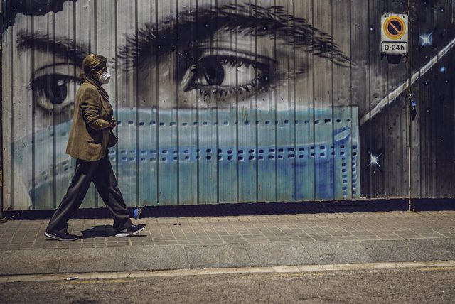 18 May 2020, Spain, Barcelona: A woman with a face mask walks past a graffiti by the city artist Shafir, which depicts a person with a mouth guard. Photo: Matthias Oesterle/ZUMA Wire/dpa