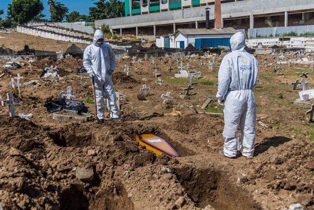 Dos trabajadores del cementerio de Sao Francisco Xavier, en Río de Janeiro, durante las labores de entierro de víctimas de la COVID-19.