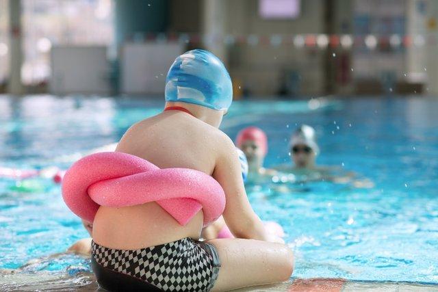 Obesidad en la infancia. Niño con flotador sentado al borde de la piscina.