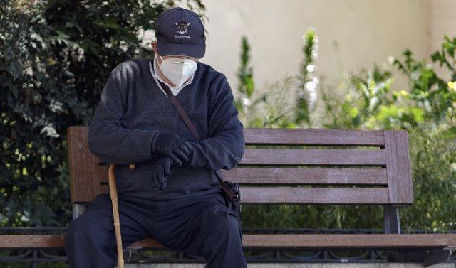 Un hombre por la calle protegido con mascarilla.