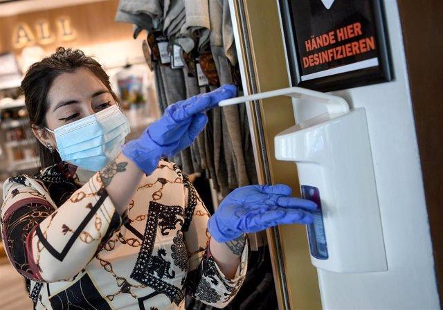 Una empleada se desinfecta con guantes en un restaurante de Berlín