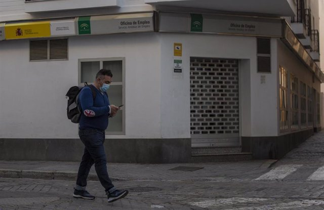 Un hombre protegido con mascarilla camina delante de una Oficina de Empleo