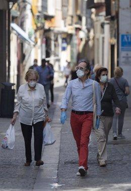 Varias personas caminan protegidas con mascarillas por una calle del centro de la ciudad, tras el nuevo acuerdo de Gobierno en el cual el uso de mascarillas será obligatorio también en la vía pública y en espacios cerrados cuando no se pueda garantizar el