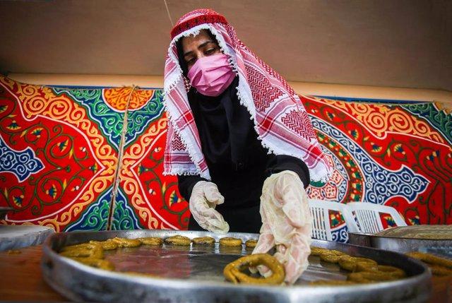 Una mujer palestina con mascarilla en Gaza preparando dulces tradicionales
