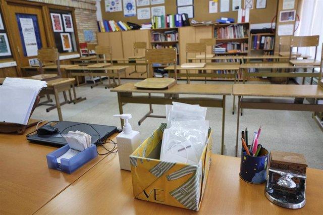 Mascarillas y gel desinfectante en la mesa del profesor de un aula donde se pueden observar los pupitres colocados y separados entre sí