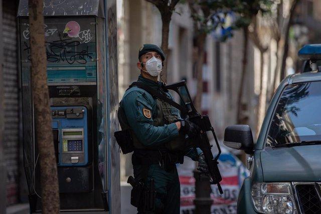 Un agente de la Guardia Civil protegido escolta las zonas cercanas a un domicilio de la calle de Josep Anselm Clavé en el distrito de Ciutat Vella de Barcelona donde han detenido a un presunto yihadista.