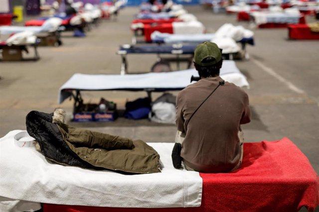 Un hombre sin hogar sentado en una de las camas del Pabellón 14 de Ifema, destinado a las personas sin hogar