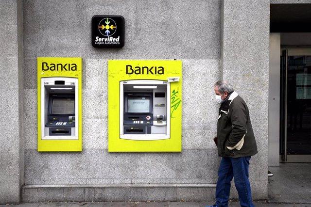 Un hombre con mascarilla pasa por delante de un cajero de Bankia.