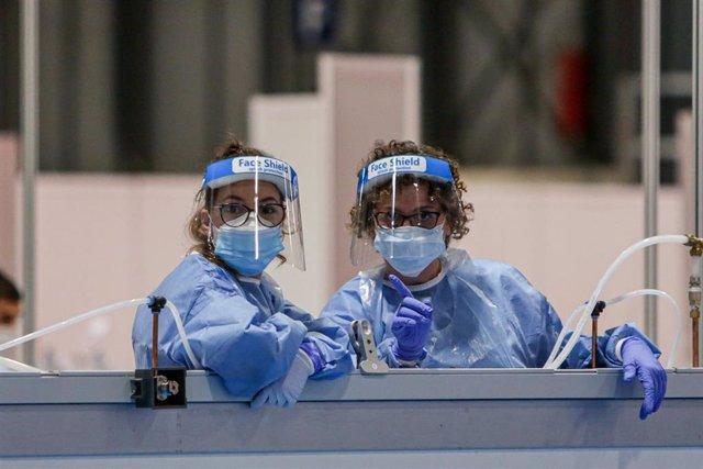 Dos sanitarias protegidas con mascarilla, guantes y pantalla protectora.