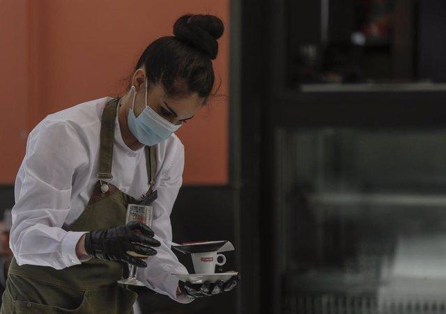 Una camarera con mascarilla y guantes atiende un bar