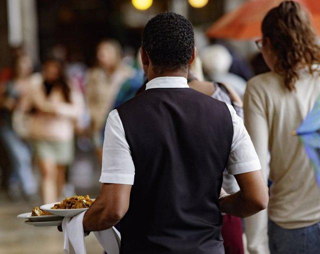 Un camarero porta los platos de los clientes en Madrid.