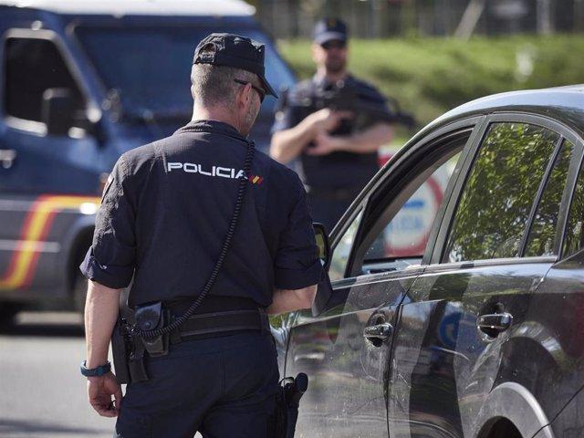Un policía nacional interroga al conductor de un vehículo en un control por el estado de alarma