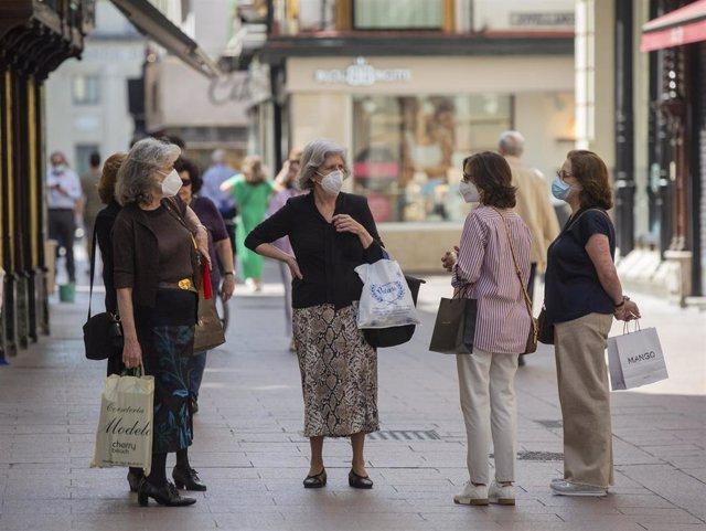 Varias personas protegidas con mascarillas conversan en una calle.