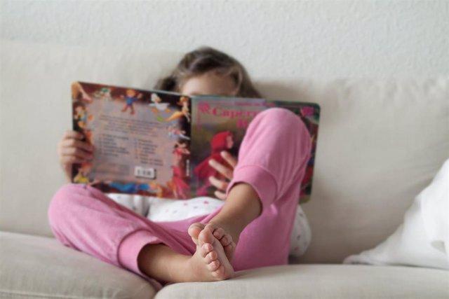 Una niña leyendo un cuento en su casa
