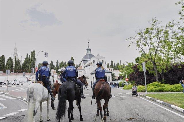 Agentes de la Unidad Equestre de la Policía Municipal de Madrid patrullan por las inmediaciones de la pradera de San Isidro.